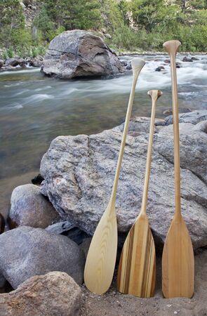 cache la poudre: three wooden canoe paddles on shore of mountain river - Cache la Poudre RIver near Fort Collins, Colorado Stock Photo