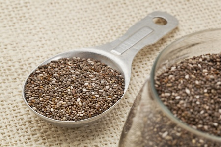 chia seeds in glass jar and on measuring aluminum tablespoon against burlap background, focus on the spoon