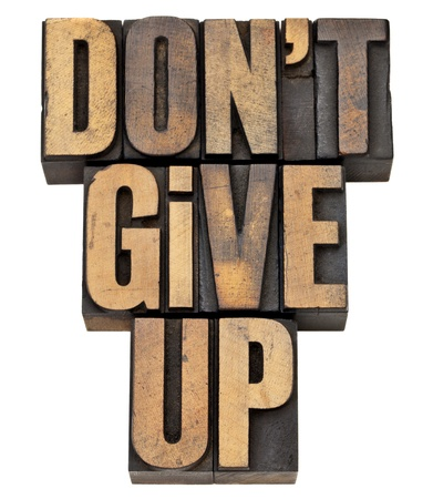 letterpress words: do not give up - motivation concept - isolated phrase in vintage letterpress wood type