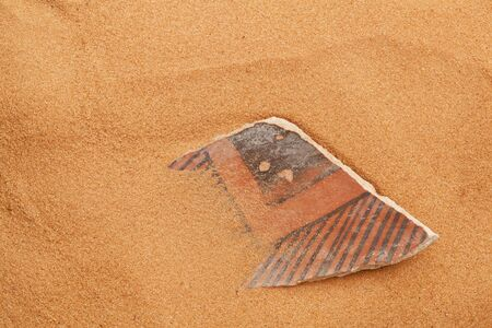 indian artifacts: ancient Anasazi pottery shard buried in red desert sand Stock Photo