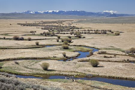 Illinois River meanders through Arapaho National Wildlife Refuge, North Park near Walden, Colorado, early spring scenery with some snow in distant mountains Stock Photo - 13559141