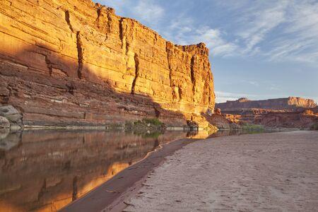 sandbar: Colorado River at sunrise in Canyonlands National Park with rock cliffs and sandbar