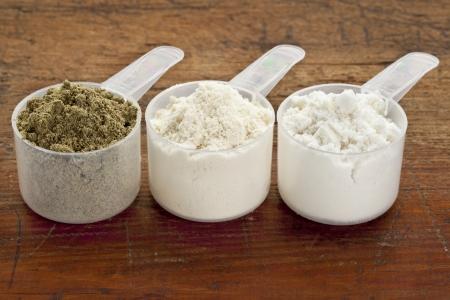 белки: пластиковые измерительные шарика трех белковых порошков из левого семян конопли, сывороточный концентрат, изолят сывороточного на гранж поверхности древесины