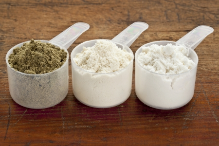 plastic measuring scoops of three protein powders  from left hemp seed, whey concentrate, whey isolate  on a grunge wood surface