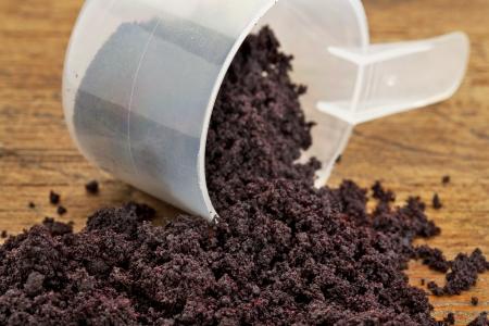 freeze dried: seca del acai berry en polvo se derrame de una cuchara dosificadora de pl�stico contra la madera de fondo del grunge