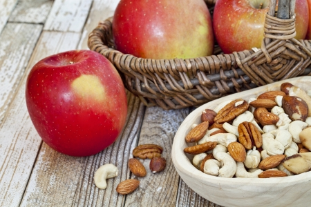 red apples and nuts  cashew, walnut, almond, Brazilian  in rustic setting  primitive wooden bowl and wicker basket over grunge painted wood surface Stock Photo - 13794937