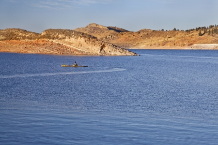sea kayak on Horsetooth Reservoir near Fort Collins, Colorado, late summer or fall scenery in sunset light photo
