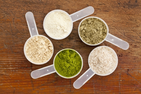 five plastic measuring cups of different superfood supplement powders (form bottom clockwise: wheatgrass, maca root, whey protein, hemp seed protein, psyllium husk) on grunge wood background Stock Photo
