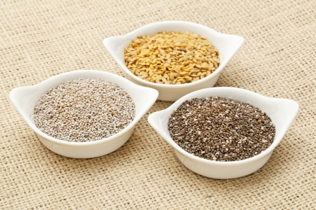 hispanica: white and brown chia and golden flax seed in white ceramic bowls against burlap canvas Stock Photo
