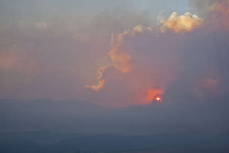 obscuring: heavy smoke from High Park wildfire obscuring the sun and sky over Rocky Mountains near Fort Collins, Colorado,  June 10, 2012 Editorial