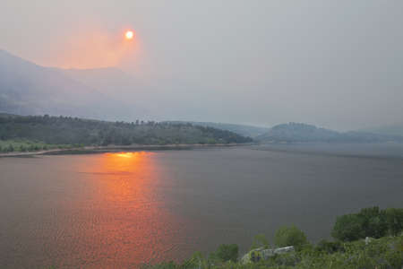heavy smoke from High Park wildfire obscuring the sun and sky over Horsetooth Reservoir and foothills near Fort Collins, Colorado, June 10, 2012 Stock Photo - 14143730