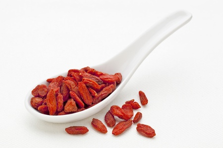 wolfberry: ceramic tablespoon of dried Tibetan goji berries (wolfberry) on  white canvas