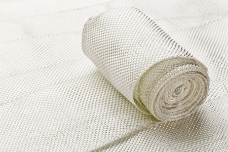 fiberglass: a small roll of fiberglass cloth tape made of twisted strands of fiberglass with woven edges