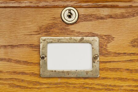 drawers: blank label in brass holder on a wooden file cabinet drawer with a lock