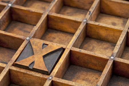 typesetter: letter X abstract - vintage letterpress printing block in grunge wood typesetter box with dividers