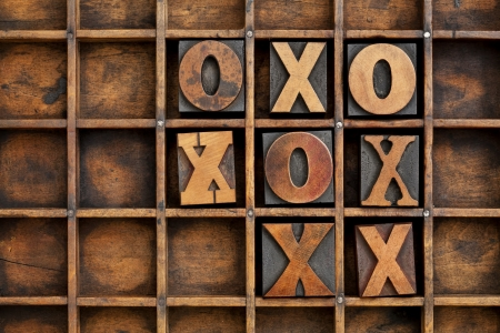 tic-tac-toe or noughts and crosses game - vintage letterpress printing block X and O in wooden grunge typesetter box with dividers Stock Photo - 14258803
