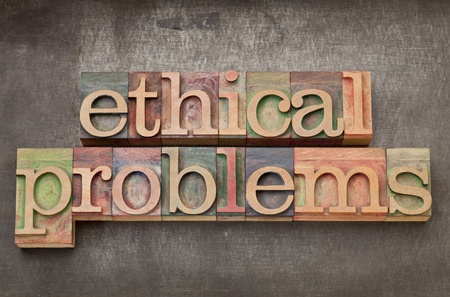 ethical problems - text in vintage letterpress wood type on a grunge metal background