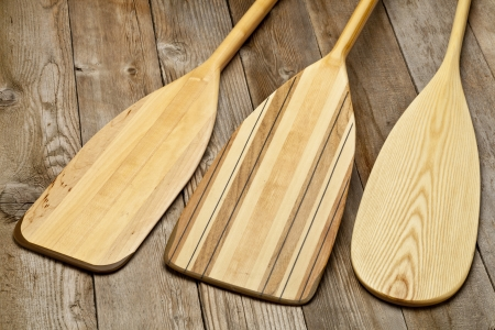 bladen van drie houten kano peddels van verschillende vorm tegen grunge houten oppervlak Stockfoto