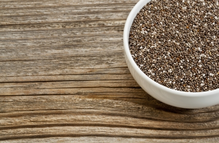 chia: chia seeds - white ceramic bowl on a grained wood, copy space