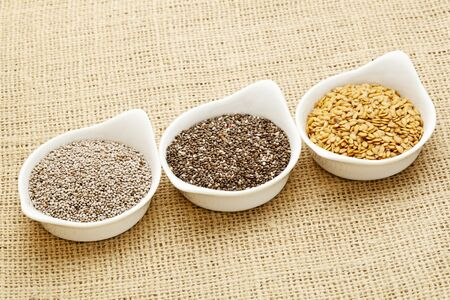 flax: white and brown chia and golden flax seed in white ceramic bowls against burlap canvas Stock Photo