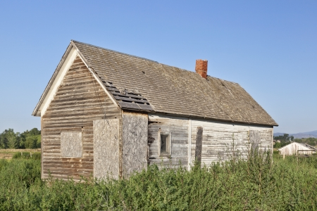 homestead: old abandoned farm house, boarded and overgrown by weeds, near Fort Collins, Colorado Stock Photo