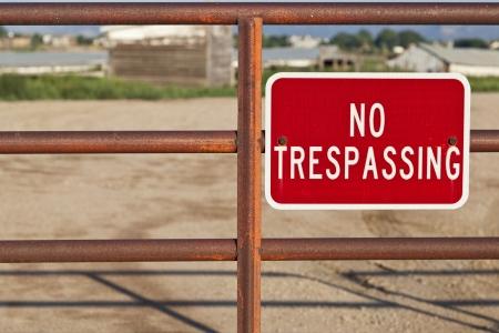 no trespassing: ninguna se�al roja entrar ilegalmente en una puerta de hierro con cabo de la construcci�n de foco detr�s de la granja