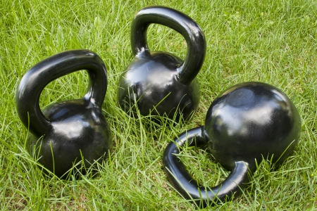 outdoor fitness: three heavy iron  kettlebells in green grass - outdoor fitness concept