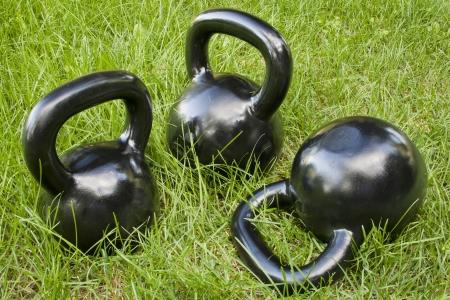 weightlifting equipment: three heavy iron  kettlebells in green grass - outdoor fitness concept