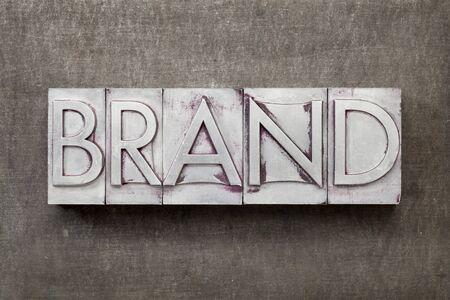 brand word in vintage letterpress metal type against a grunge steel sheet Stock Photo - 14461861