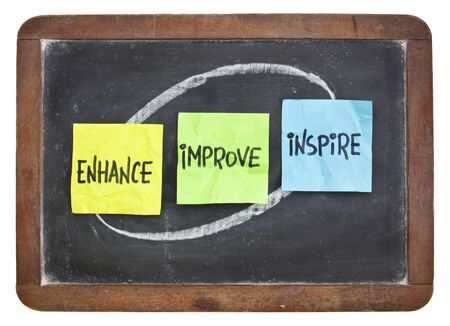 enhance: enhance, improve, inspire - motivation and inspiration concept - colorful sticky notes on a slate blackboard Stock Photo