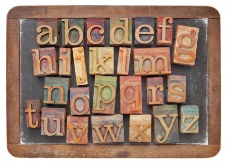 English alphabet in vintage letterpress wood type on an old slate blackboard