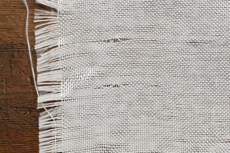 edge of woven cloth on a grunge wood background photo
