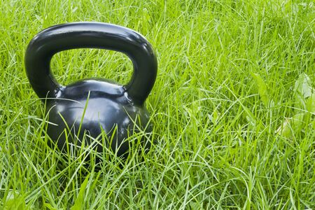 heavy iron black kettlebell in green grass - outdoor fitness concept photo