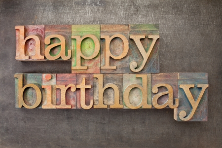 happy birthday - text in vintage letterpress printing blocks against a grunge metal sheet photo