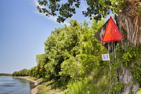 mileage: red navigational sign and mileage on left shore of Missouri River