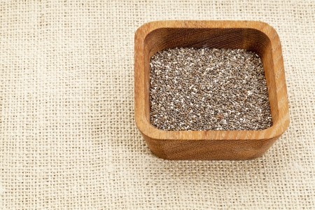 chia seeds in square wooden bowl against burlap canvas