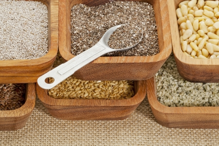 hispanica: chia and other healthy seeds (gold and brown flax, hemp. pine nuts) in wooden bowl with measuring tea spoon Stock Photo