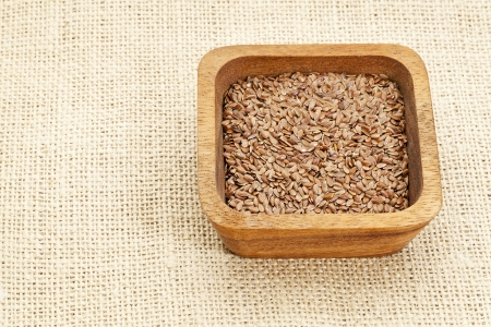 brown flax seeds in square wooden bowl against burlap canvas Stock Photo - 14992320