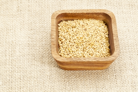 gold flax seeds in square wooden bowl against burlap canvas Stock Photo - 14992311
