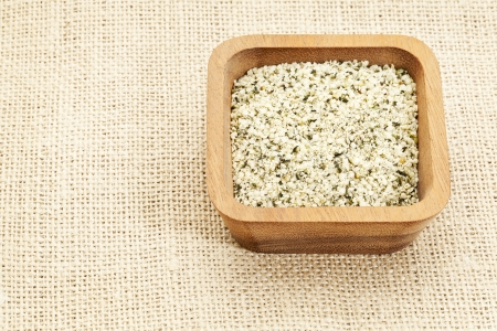 shelled: shelled hemp seeds in square wooden bowl against burlap canvas
