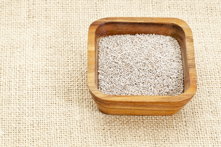 white chia seeds in square wooden bowl against burlap canvas Stock Photo - 14992319