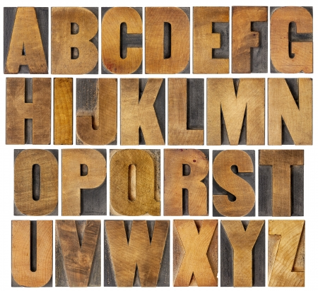 complete English alphabet - collage of 26 isolated vintage wood letterpress printing blocks, scratched and stained by ink patina, gothic bold extended font Stock Photo