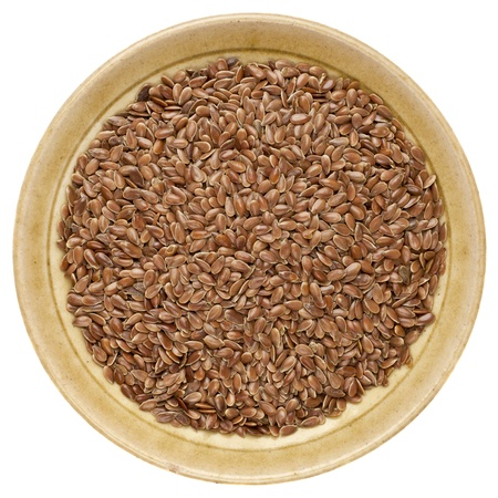 brown flax seeds in a round ceramic bowl isolated on white Stock Photo - 15031372