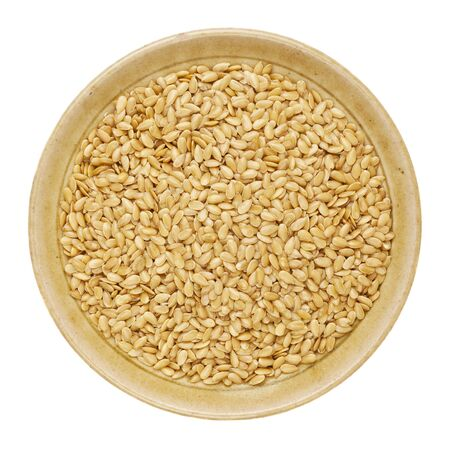 gold flax seeds in a round ceramic bowl isolated on white Stock Photo - 15488390