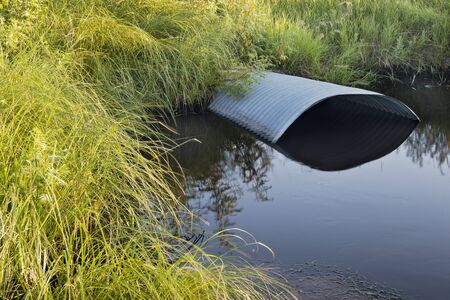 culvert: green meadow and irrigation ditch with culvert Stock Photo