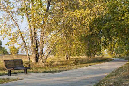 loveland: bench and recreational biking trail in Boyd Lake State Park near Loveland, Colorado, fall scenery