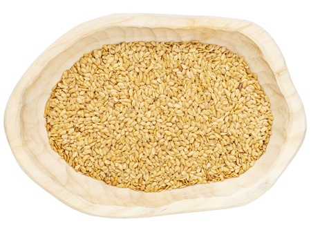 flax: golden  flax seeds in a rustic wood bowl isolated on white