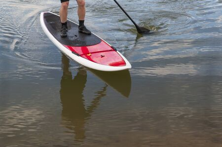 paddler: paddling stand up paddleboard on a lake - feet and legs of male paddler