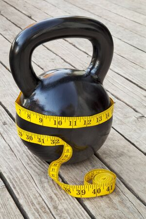 kettlebell and measuring tape on wooden deck - fitness and diet concept Stock Photo - 15934812