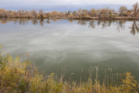 pit fall: gravel pit converted into natural area - Riverbend Ponds, Fort Collins, Colorado in late fall scenery with residential homes in background Stock Photo